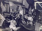 Women wave American flags and blow horns in celebration. Bryn Mawr College