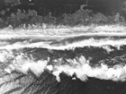 aerial view of breaking waves and overwash on sandy beach