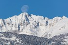 Electric Peak is covered with snow below a full moon on a blue sky day.