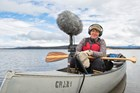 Jennifer Jerrett records sounds in a canoe on a lake.
