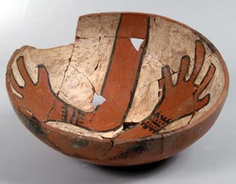 ancestral pueblo bowl with a chipped rim, depicting two hands inside the bowl