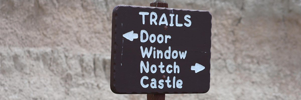a brown sign with white writing points to door, window, notch, and castle trails.