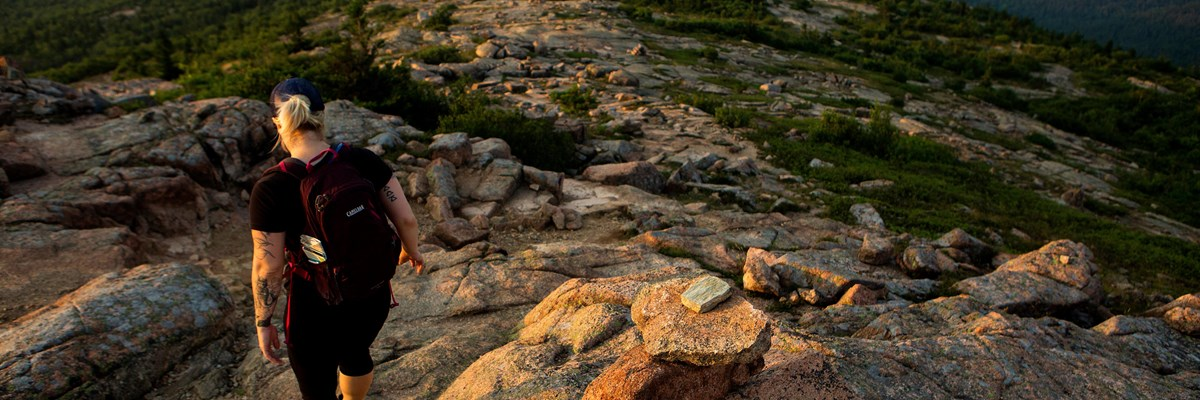 Visitor hikes down granite trail marked with cairns