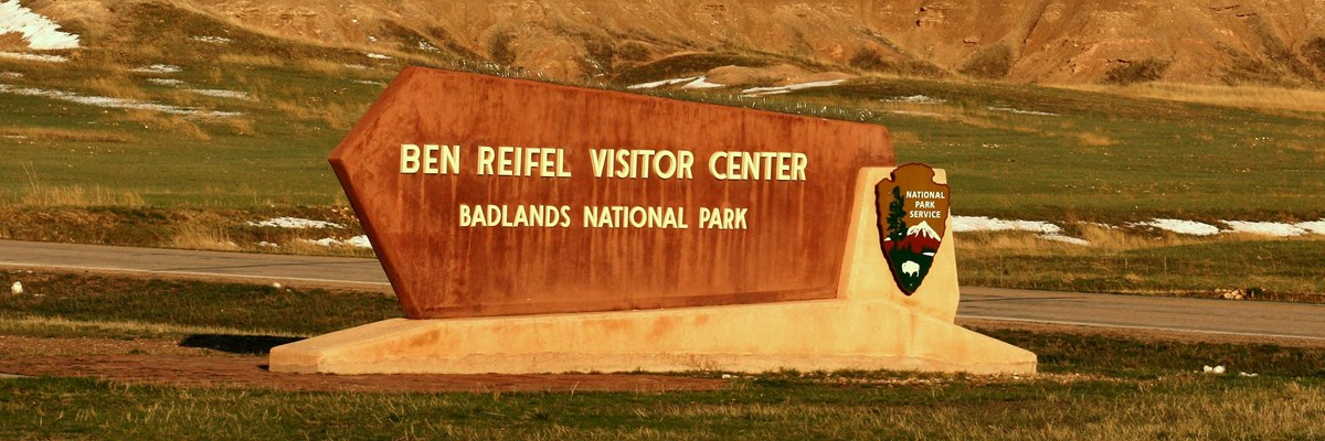 a sign reading ben reifel visitor center sits in front of jagged badlands formations.