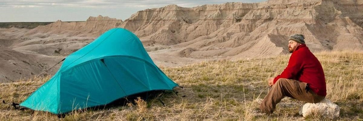 a hiker in a red jacket sits next to a blue tent with badlands buttes in the background