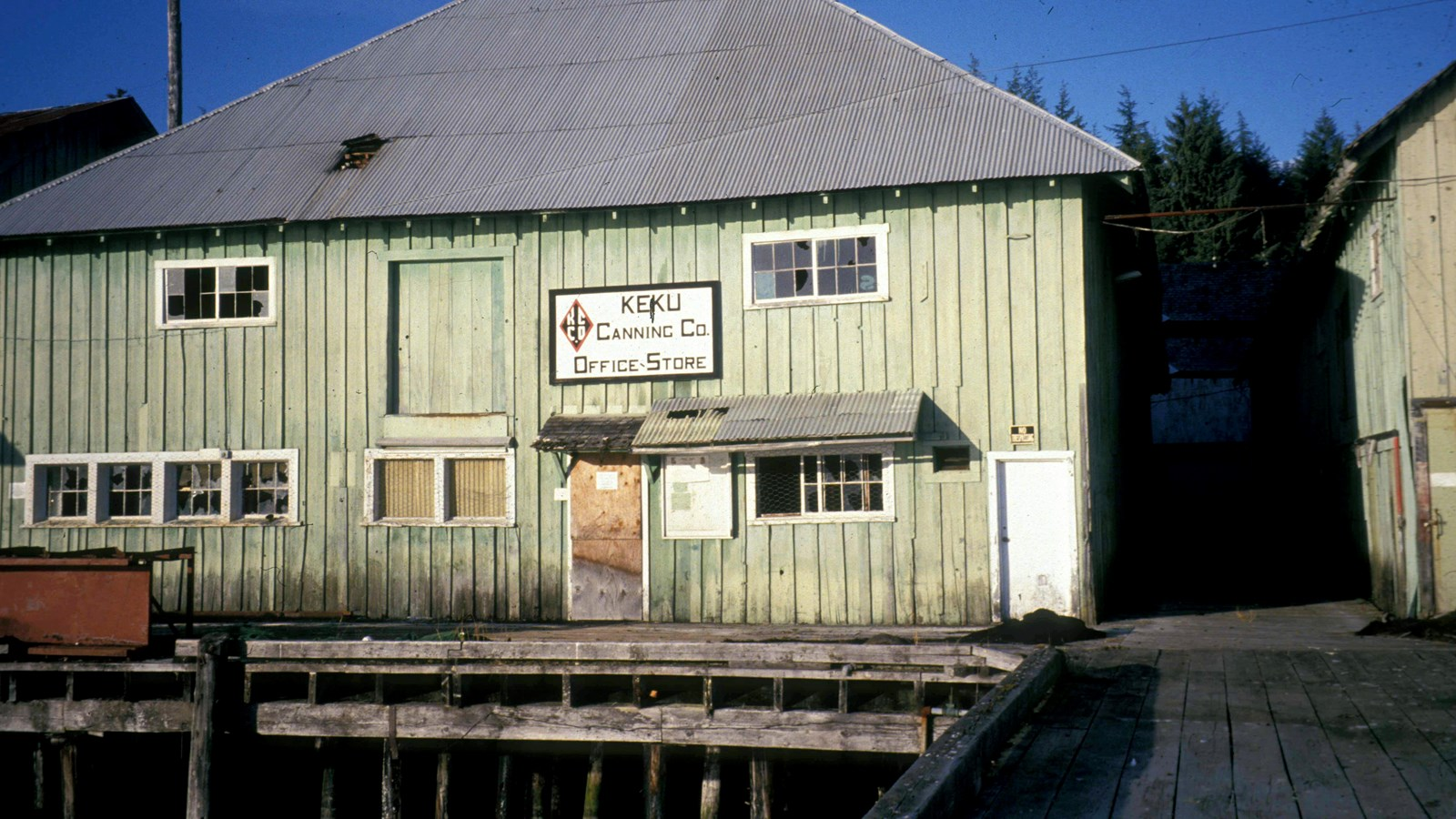 The Keku Cannery Office and Store in a faded green building on a pier.