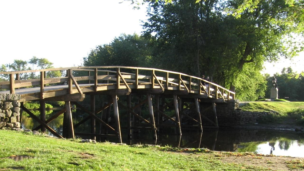 Arched wooden bridge with field stone abutments spans a slow river bounded by green embankments