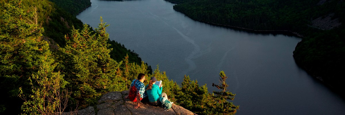 Visitors sitting on a rock ledge overlooking a lake