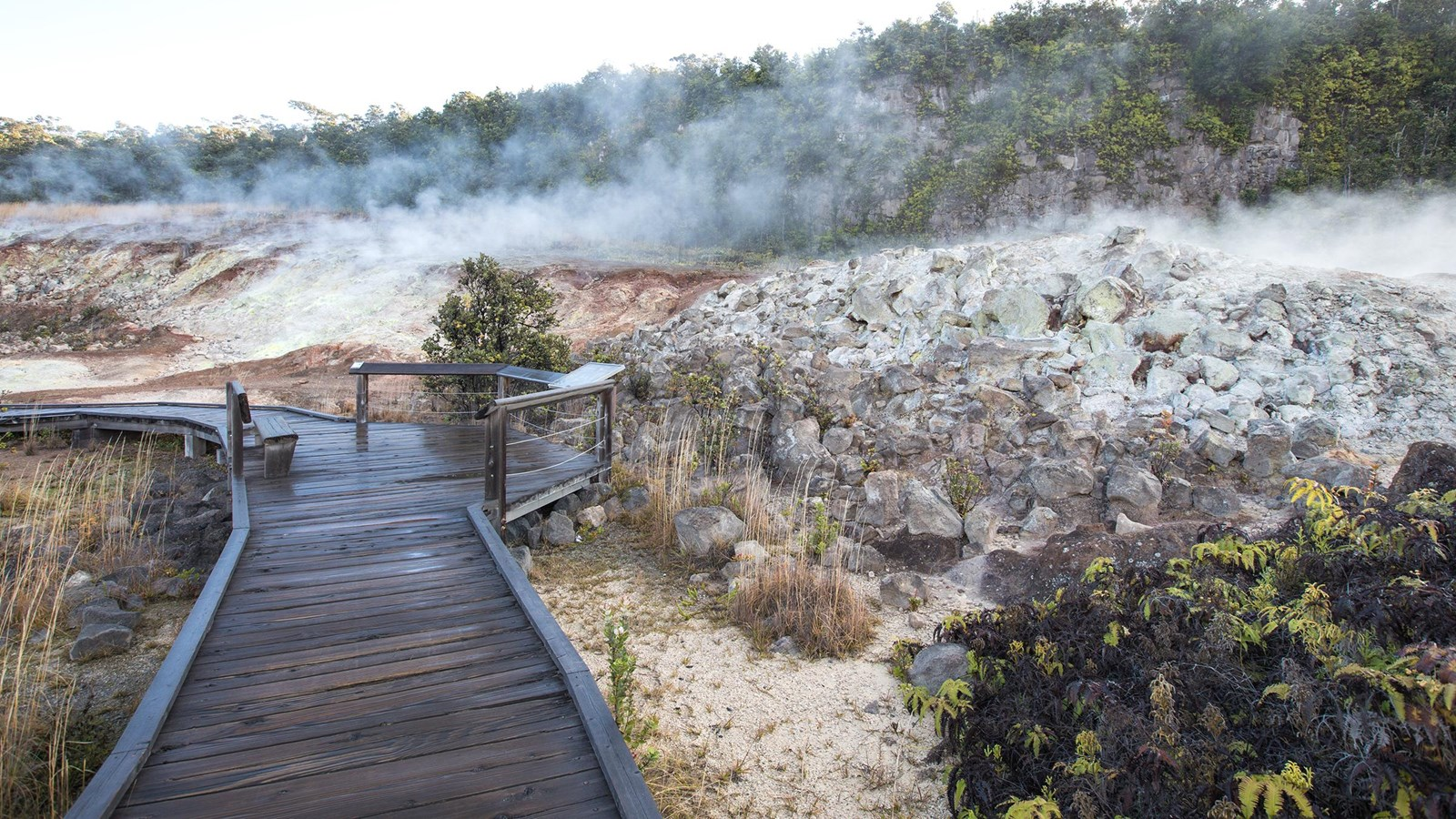 Steam rises from mineral deposits in front of a boardwalk