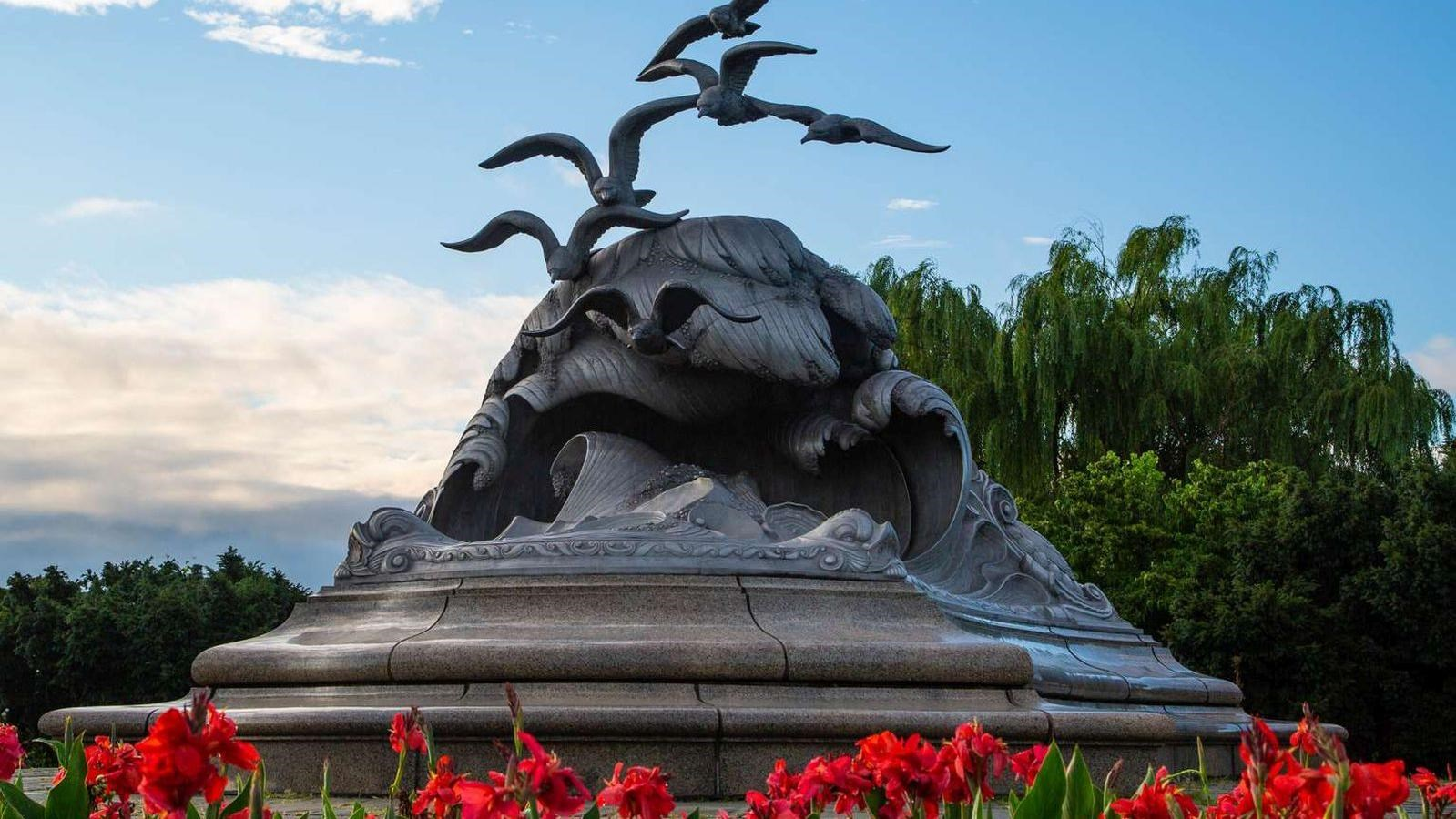 Statue of waves and seagulls surrounded by red flowers