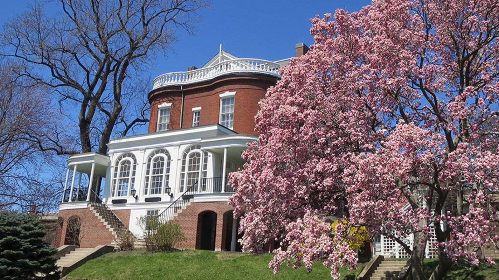 Commandant House, a red brick and white wood Federalist Style structure next to a blooming tree.