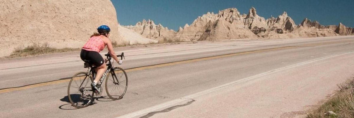 a woman bikes up a paved road with jagged badlands spires in the background