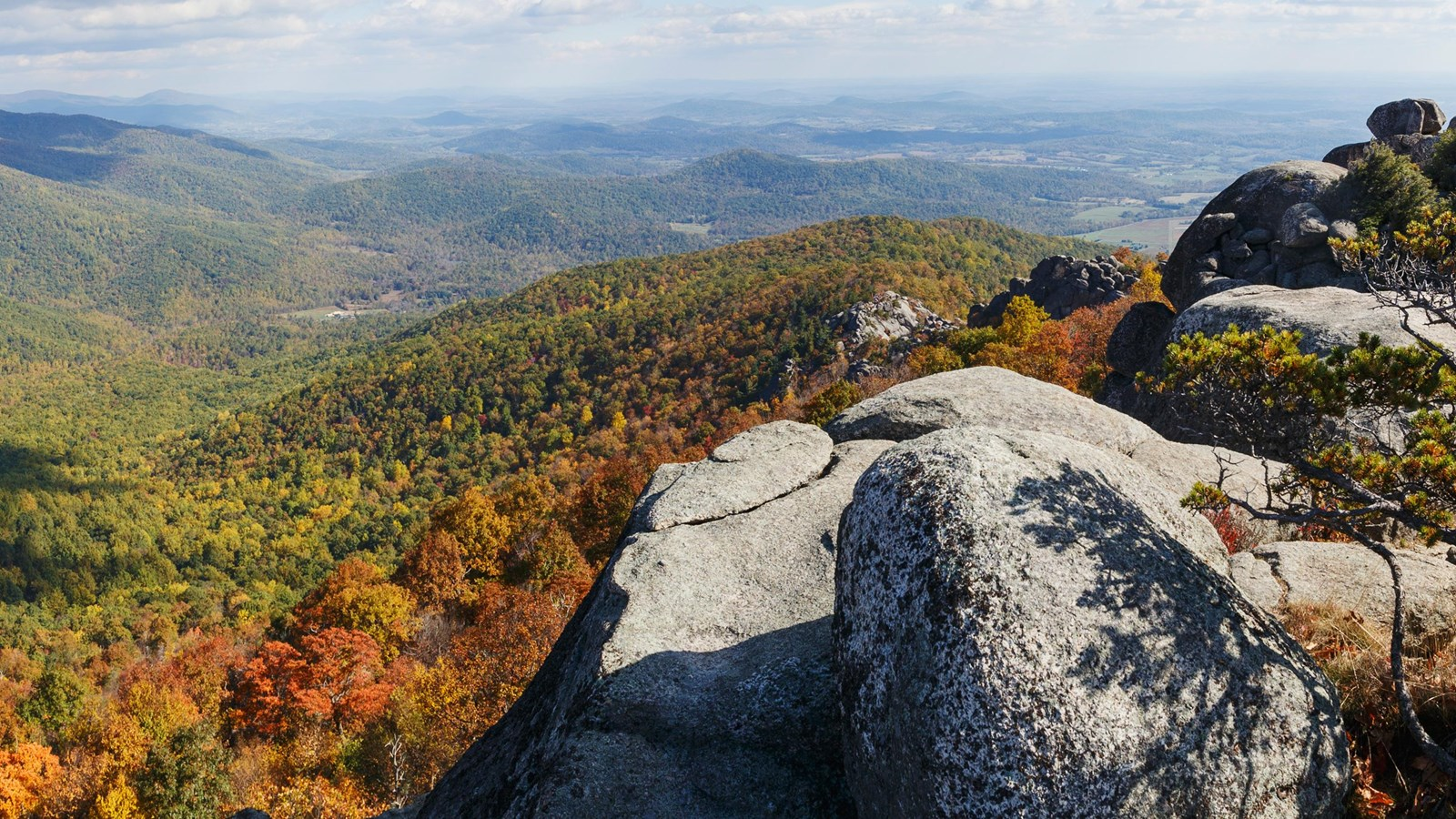 A rock outcrop overlooks mountain layers below, exploding with fall colors: red, orange, and yellow