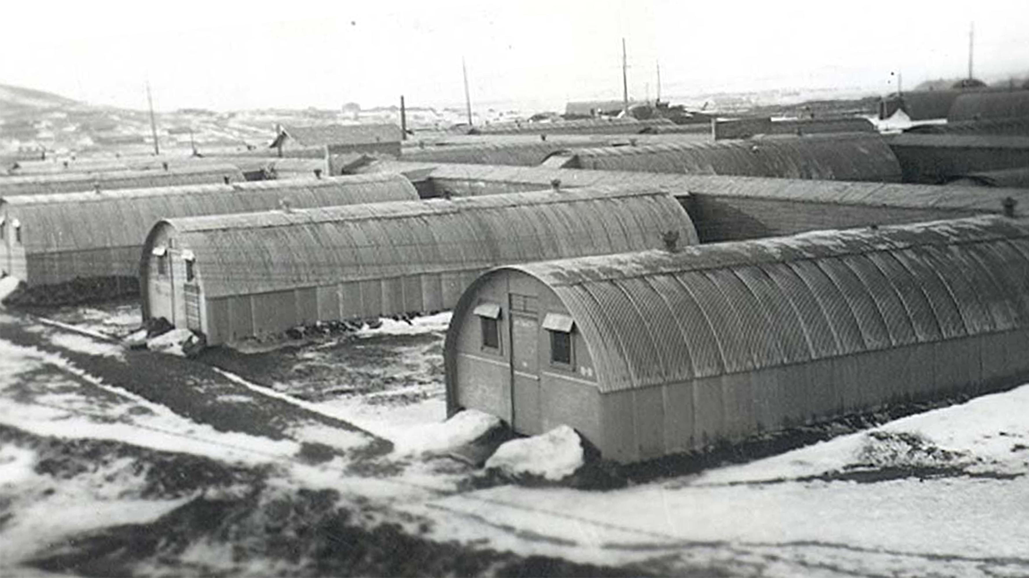 Historic photo of rows of long Quonset huts.
