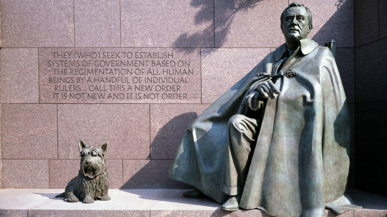 A bronze sculpture of seated Franklin Roosevelt with a cloak obscuring his chair, with his dog Fala.