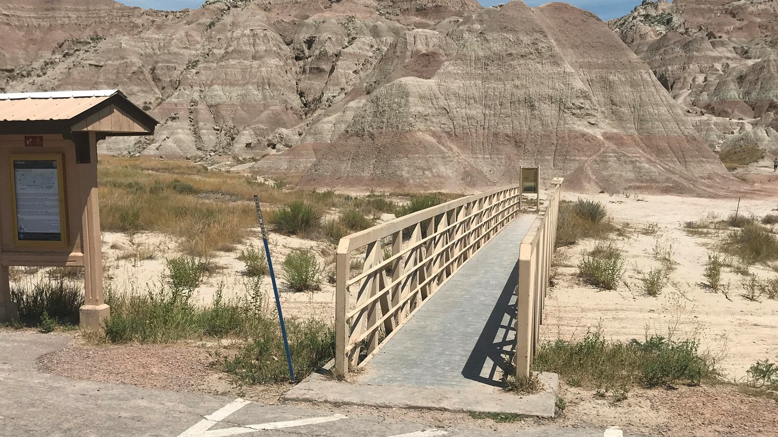 Information board sits alongside boardwalk which extends into badlands formations under blue sky.