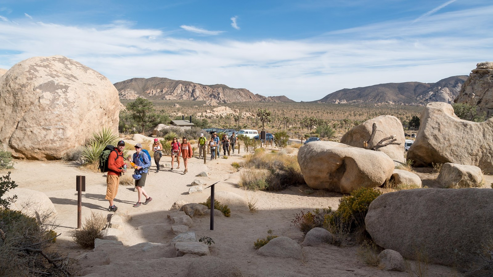 A group of hikers heading up a dirt trail between large rocks with mountains in the background.