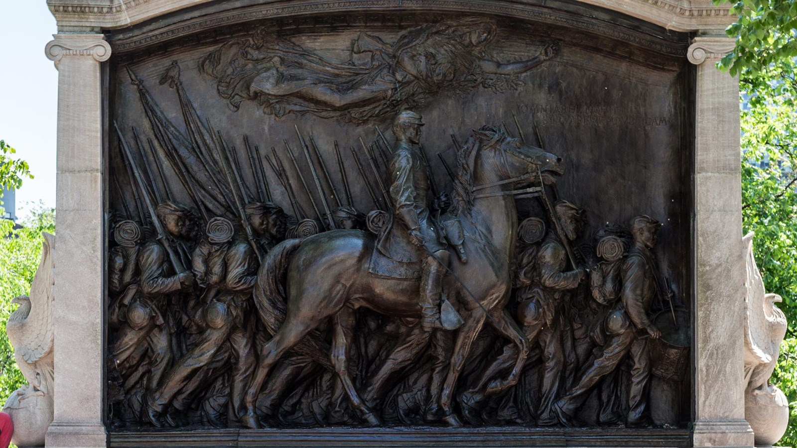 Monument of a man on a horse with multiple soldiers marching around him.