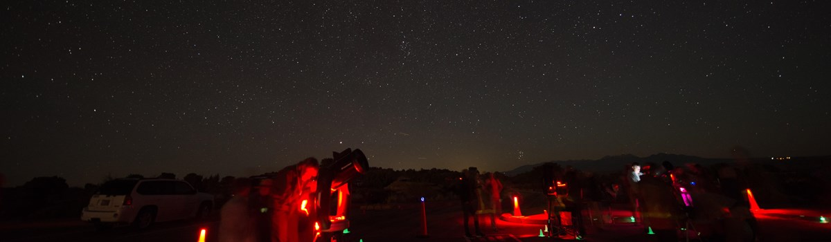 telescopes illuminated red beneath a star-filled sky