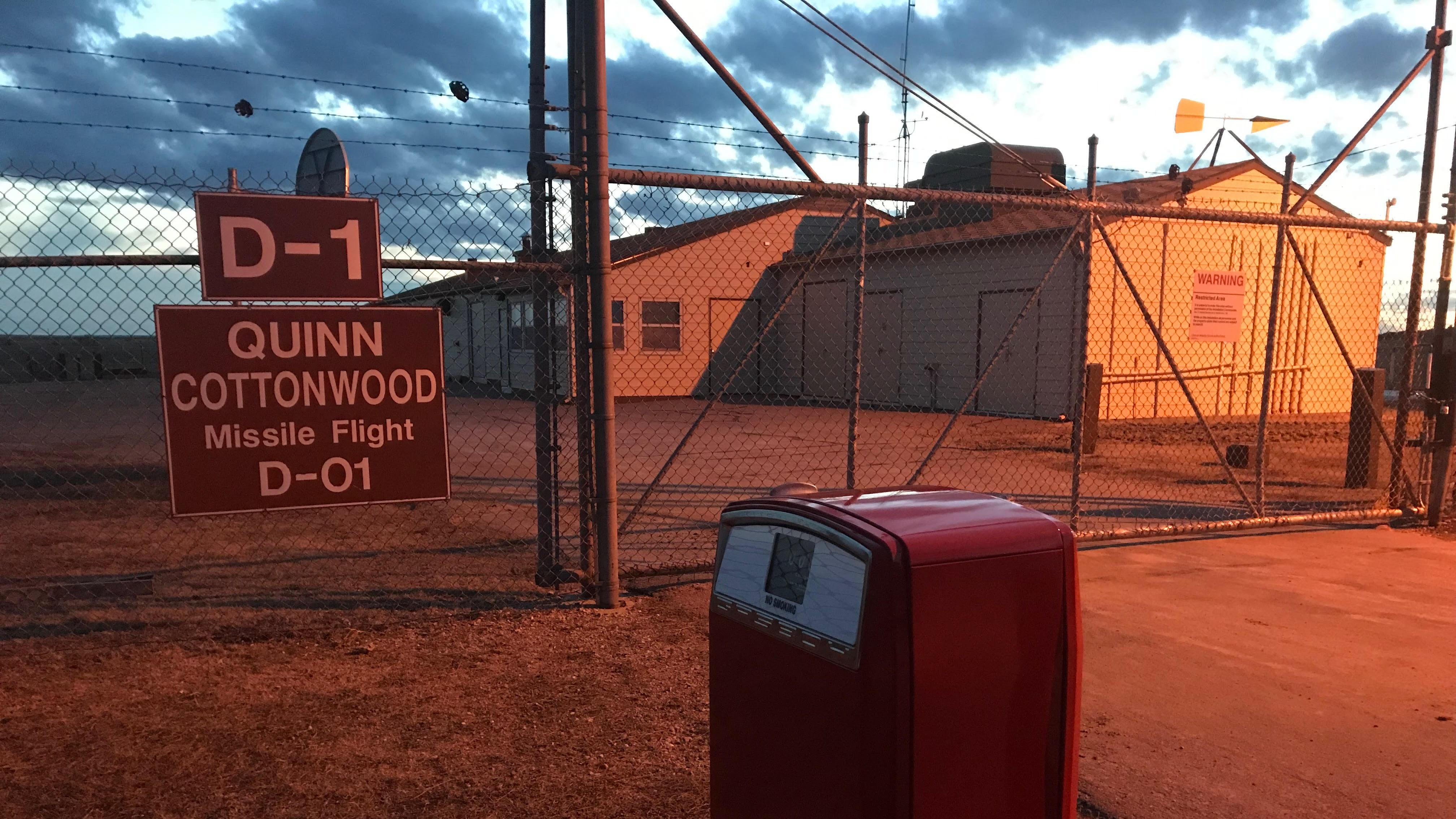 a red gas pump stands outside a fenced compound with a large tan building