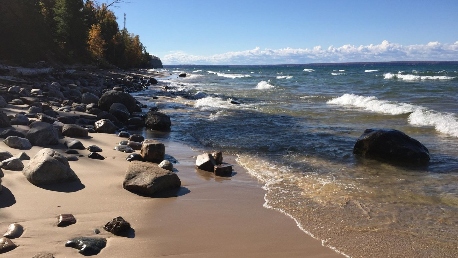 small and medium sized boulders and rocks on the beach and in the water.