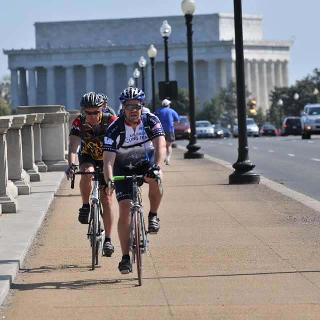 Cyclists cross Arlington Memorial Bridge.