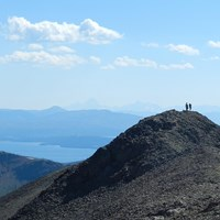Two hikers enjoying the view from the summit of Avalanche Peak.