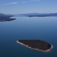 An aerial view of an island in the blue waters of Lake Clark