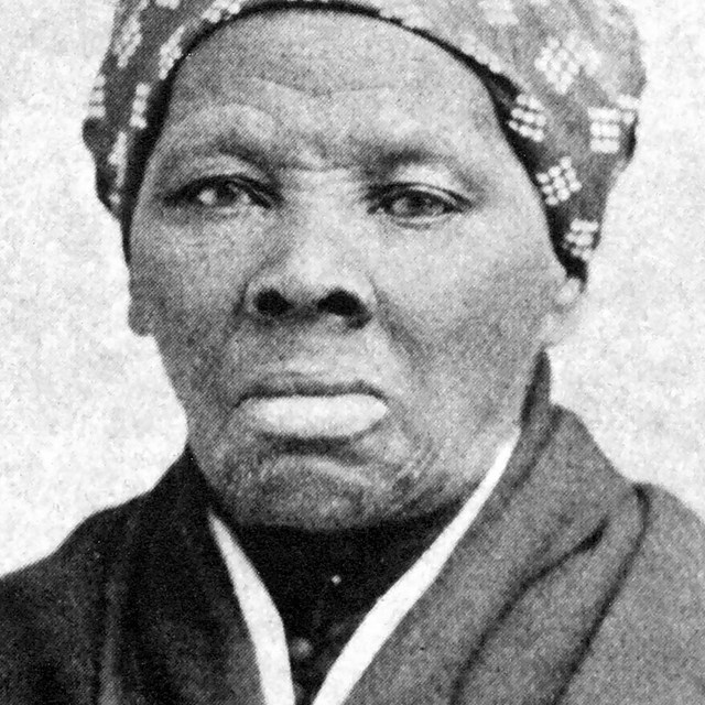 A black and white image of Harriet Tubman. She is looking at the camera. A kerchief on her head.