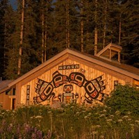 a large building with traditional alaska native carvings on the front at sunset