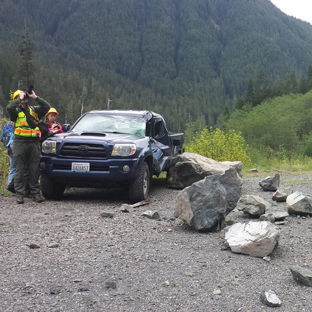 a vehicle damaged by rockfall on backcountry road