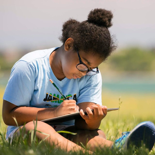 Young girl writing on a clipboard, sitting outside in the grass.