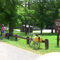 bicyclists stopped along a natural surface path near a modern and an historic historic