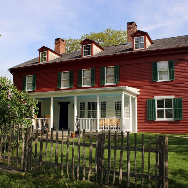 A large red house, 2 stories tall, with a sloped black roof, green shutters, and a white porch.