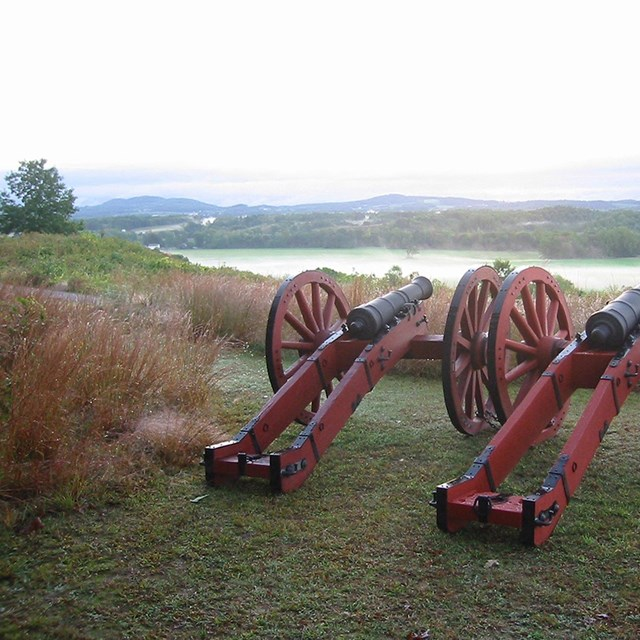 2 red field cannons sitting on a bluff overlooking the Hudson River. It cuts a green valley in half.