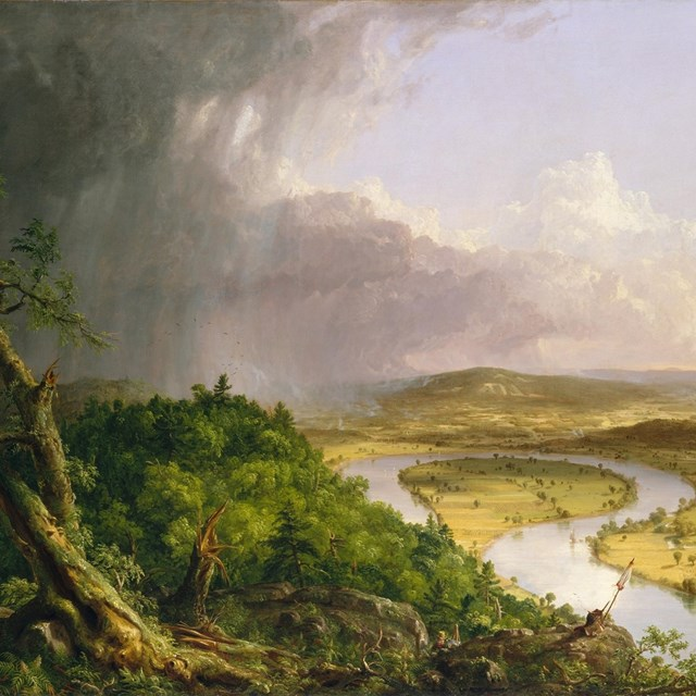 An oil landscape painting. A view from a green bluff of a single tree & a river oxbow in sunlight.