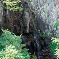 A view from across a ravine of a tall, thin waterfall.