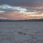 A vast salt flat stretches into the horizon with a cloudy sunset sky.