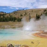 Steam rises from a blue-, yellow-, and orange-colored hot spring.
