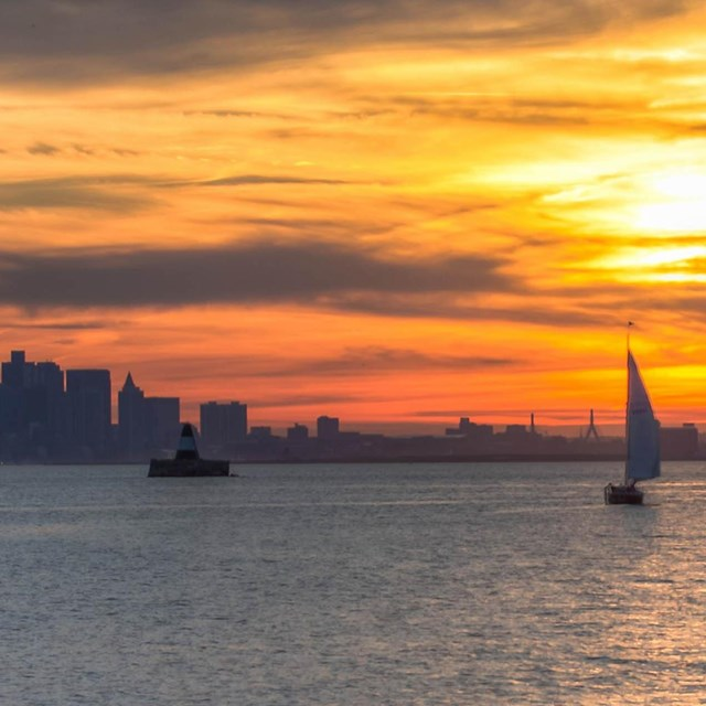 A fiery sunset over water. Reds, yellows, reds, & blues fade to grey of a city skyline and sailboat.