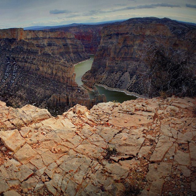 A massive canyon with multicolored walls and a river far below.