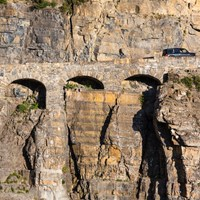 Car drives uphill over triple arched stone bridge