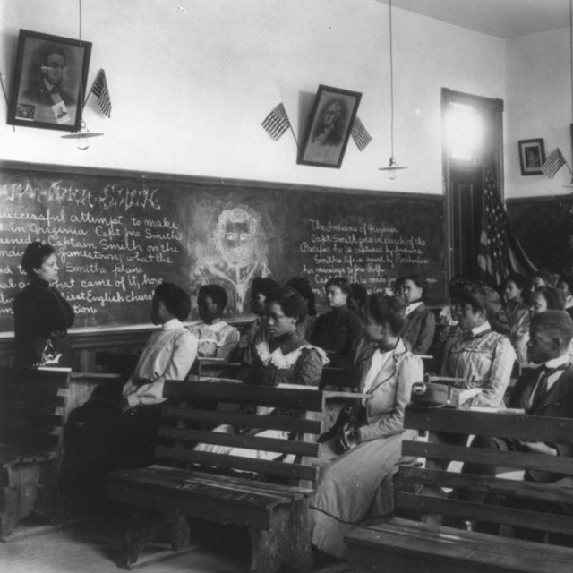 An all African American class look at a teacher standing by a chalkboard; B&W Photo