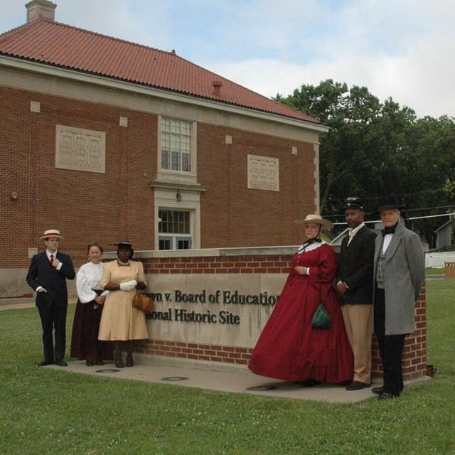 people in period dress stand in front of park sign
