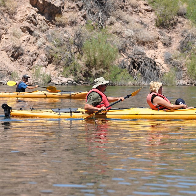 Three people padding kayaks on desert river