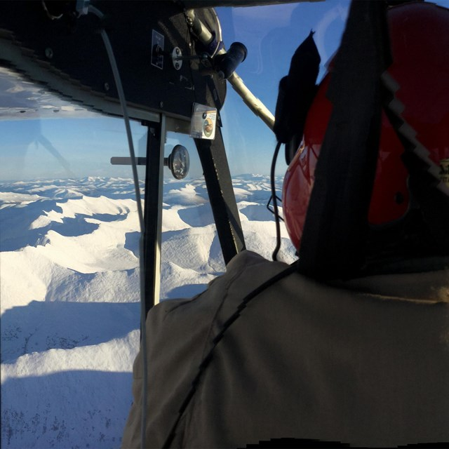 A pilot with a red helmet on, flying a plane high above snowy terrain