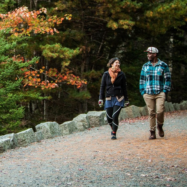 A man and woman stroll along a carriage road in Acadia with leaves turning to fall colors overhead.