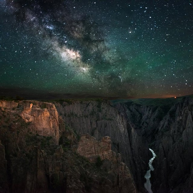 A dark, star-filled sky and Milky Way arch over Black Canyon of t he Gunnison National Park