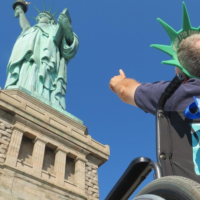 Visitor sitting and pointing at the Statue of Liberty.