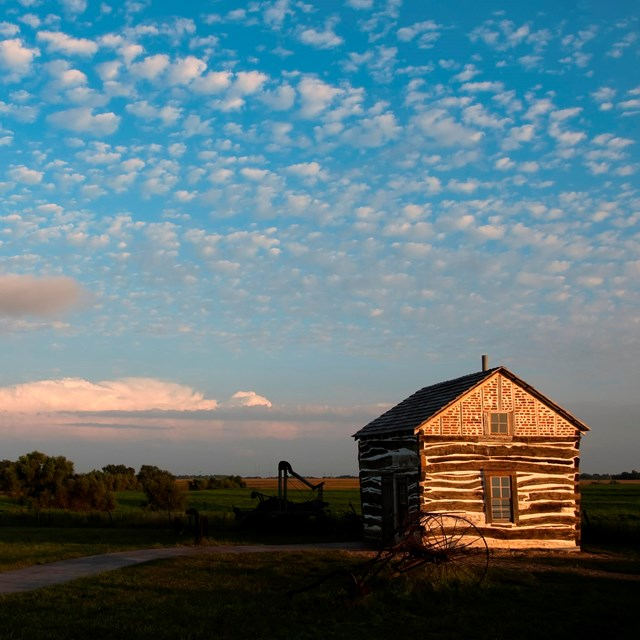 A square log cabin sits to the left of an expanse of prairie.
